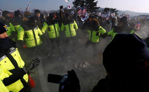 Police rush to extinguish burnt portraits of North Korean leader Kim Jong Un during an anti-North Korea protest before the opening ceremony for the Pyeongchang 2018 Winter Olympics in Pyeongchang - Credit: Edgar Su/Reuters