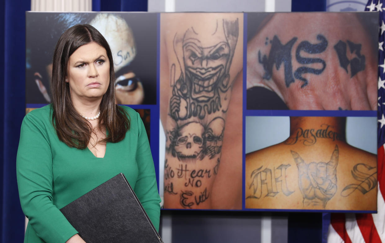 White House press secretary Sarah Sanders stands in front of pictures of MS-13 gang tattoos during a press briefing in July 2017. (Photo: Alex Brandon/AP)