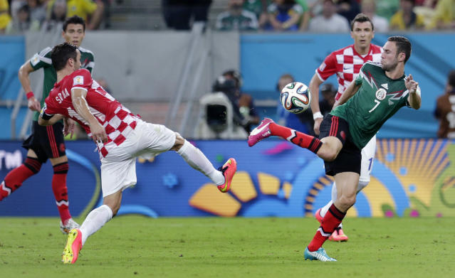 Mexico's Miguel Layun, right, and Croatia's Darijo Srna battle for the ball during the group A World Cup soccer match between Croatia and Mexico at the Arena Pernambuco in Recife, Brazil, Monday, June 23, 2014. (AP Photo/Petr David Josek)