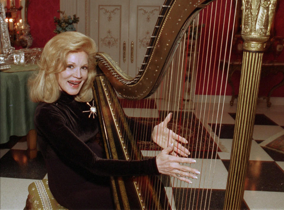 FILE - In this Tuesday, Dec. 12, l995 file photo, Phyllis McGuire, the youngest of The McGuire Sisters, plays a harp at her home in Las Vegas. Phyllis McGuire, the last surviving member of the three singing McGuire Sisters who topped the charts with several hits in the 1950s, has died, Tuesday, Dec. 31, 2020. She was 89. (AP Photo/Lennox McLendon, File)