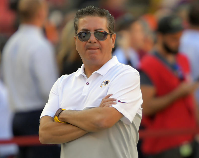 Dan Snyder stands on a football field.