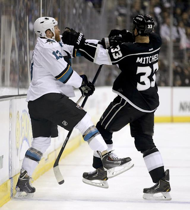 San Jose Sharks left wing Raffi Torres, left, and Los Angeles Kings defenseman Willie Mitchell fight during the first period in Game 4 of an NHL hockey first-round playoff series in Los Angeles, Thursday, April 24, 2014. (AP Photo/Chris Carlson)
