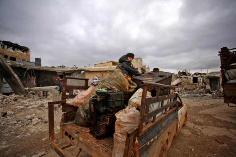 Syrians flee with belongings that they salvaged from the rubble of their home levelled by an air strike on the west Aleppo village of Kafr Nuran