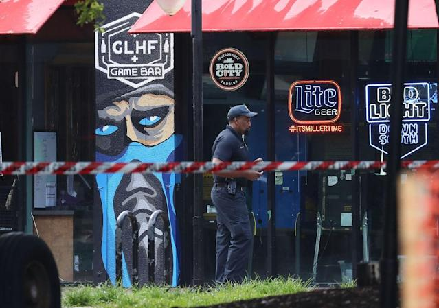 "A Jacksonville Sheriff officer walks past the GLHF Game Bar where two ""Madden"" competitors were killed in Jacksonville on Sunday. (Getty Images)"