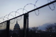 The Capitol dome is seen beyond a perimeter security fence topped with razor wire in Washington, early Thursday, March 4, 2021. (AP Photo/Carolyn Kaster)