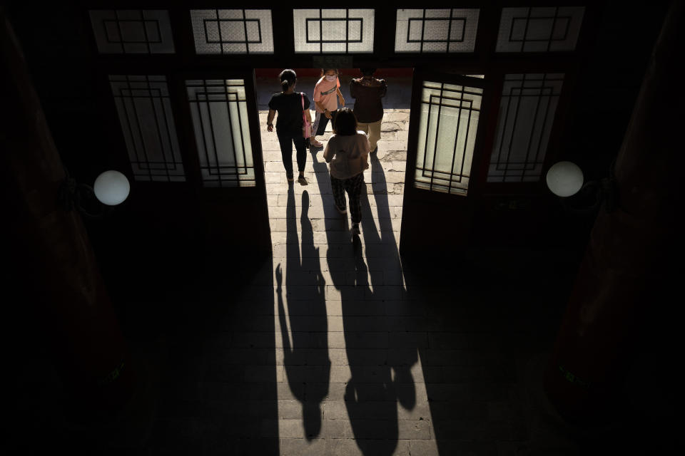 Visitors wearing face masks to protect against COVID-19 cast shadows as they walk out of a restored tower at a park on a historic section of the old city wall in Beijing, Saturday, Aug. 28, 2021. (AP Photo/Mark Schiefelbein)