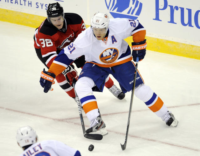 New Jersey Devils' Damon Severson, left, pokes the puck away from New York Islanders' Kyle Okposo during the second period of a preseason NHL hockey game, Thursday, Sept. 19, 2013, in Newark, N.J. (AP Photo/Bill Kostroun)