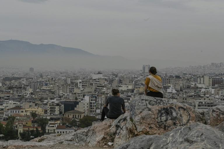 Tourists sit at Aeropagus hill overlooking foggy Athens on Tuesday as cafes, bars and restaurants closed due to a partial lockdown to reverse a resurgent Covid-19.