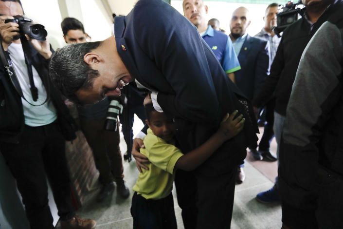 Opposition leader Juan Guaido, who has declared himself interim president of the country, embraces a child at the end of a press conference at a school where he delivered humanitarian aid, in Caracas, Venezuela, Thursday, March 21, 2019. (AP Photo/Natacha Pisarenko)