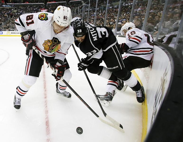 Los Angeles Kings defenseman Willie Mitchell, middle, battles Chicago Blackhawks right wing Marian Hossa, left, and left wing Patrick Sharp for the puck during the third period of Game 4 of the Western Conference finals of the NHL hockey Stanley Cup playoffs in Los Angeles, Monday, May 26, 2014. The Kings won 5-2. (AP Photo/Chris Carlson)