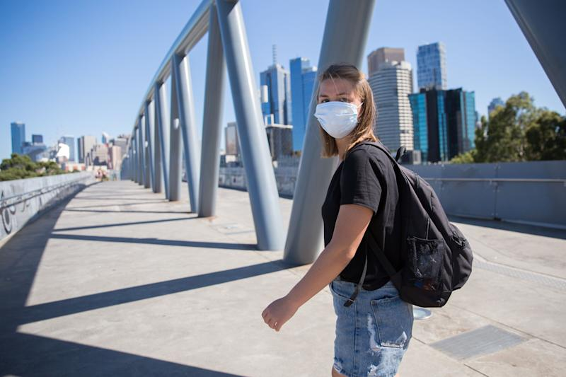 Young woman wearing a face mask walking through the streets of Melbourne, Australia on a sunny day (Photo: CraigRJD via Getty Images)