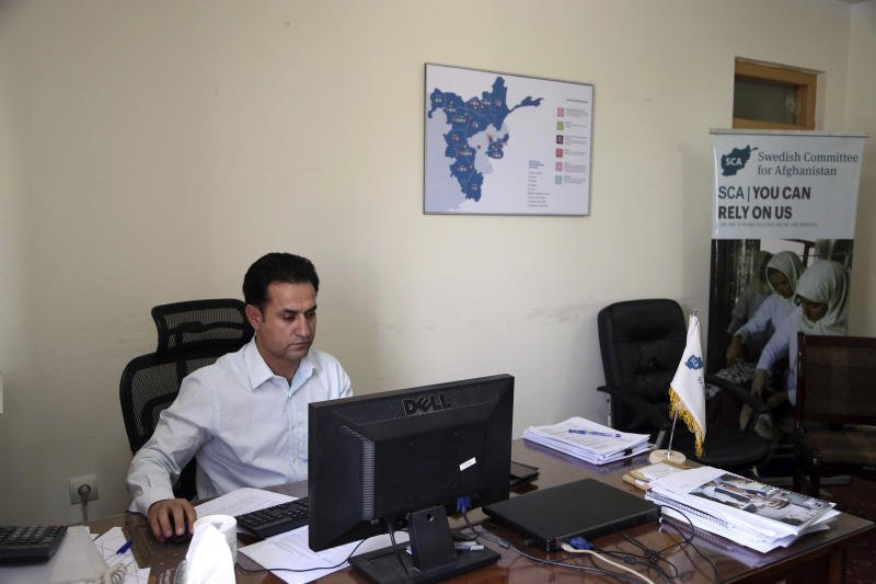 Ahmad Khalid Fahim, program director for the Swedish group, works at his desk, during an interview with the Associated Press in Kabul, Afghanistan, Wednesday, July 17, 2019. A Swedish non-governmental organization in Afghanistan says the Taliban have forced the closure of 42 health facilities run by the non-profit group in eastern Maidan Wardan province. (AP Photo/Rahmat Gul)