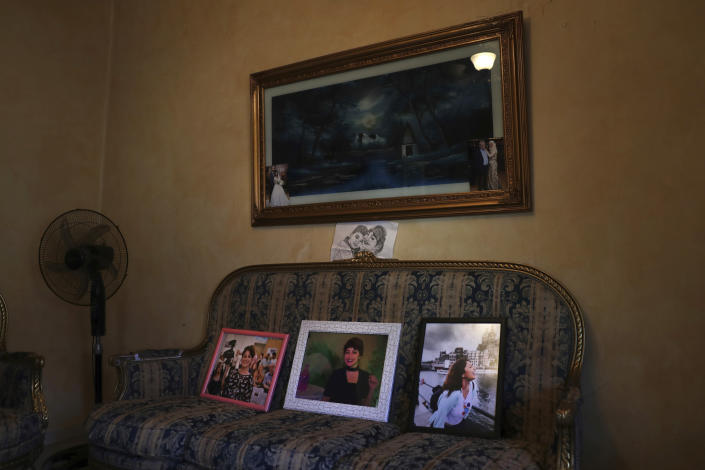 """In this Nov. 17, 2019 photo, the family of Nadyn Jouny displays photos of her, at a 40 day mourning ceremony of her death in a car accident, at their family house in southern Beirut, Lebanon. In death as in life, Jouny -- affectionately called Om Karam, Arabic for """"mother of Karam"""" -- has showcased the struggles of Lebanese women who are battling laws that give religious courts say over many aspects of their lives. (AP Photo/Hassan Ammar)"""