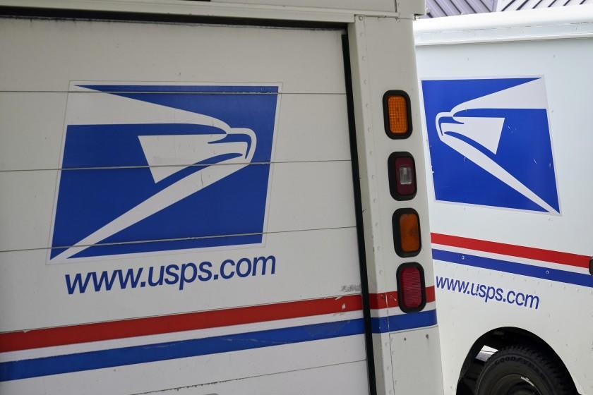 FILE - In this Aug. 18, 2020, file photo, mail delivery vehicles are parked outside a post office in Boys Town, Neb. The United States Post Office said Tuesday, Feb. 23, 2021 that it has chosen Oshkosh Defense to build its next-generation mail-delivery vehicle, part of an effort to make the USPS more environmentally friendly by switching a portion of its huge fleet to electric vehicles. (AP Photo/Nati Harnik, File)