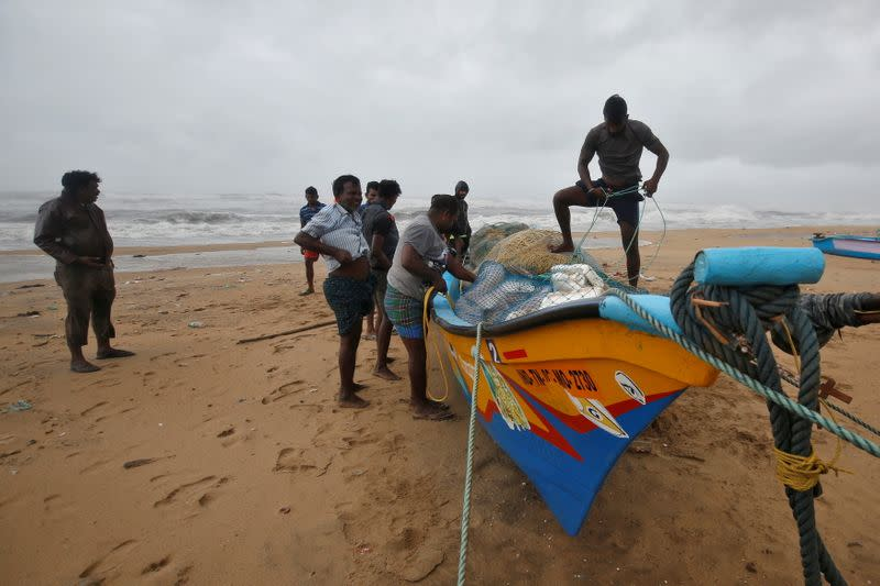 Fishermen tie their boat on the shore before Cyclone Nivar's landfall, in Chennai