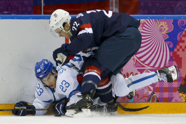 Finland forward Sakari Salminen and USA defenseman Kevin Shattenkirk crash the boards during the first period of the men's bronze medal ice hockey game at the 2014 Winter Olympics, Saturday, Feb. 22, 2014, in Sochi, Russia. (AP Photo/Mark Humphrey)