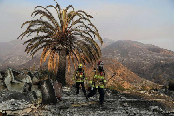 PHOTO: Firefighters Jason Toole, right, and Brent McGill with the Santa Barbara Fire Dept. walk among the ashes of a wildfire-ravaged home after turning off an open gas line, Nov. 10, 2018, in Malibu, Calif. (Marcio Jose Sanchez/AP)