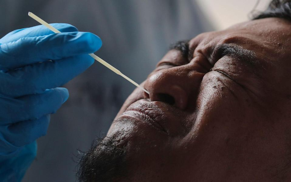 A man reacts as medical personnel take a swab sample for coronavirus testing at MSU Medical Centre in Shah Alam, Malaysia - FAZRY ISMAIL/EPA-EFE/Shutterstock