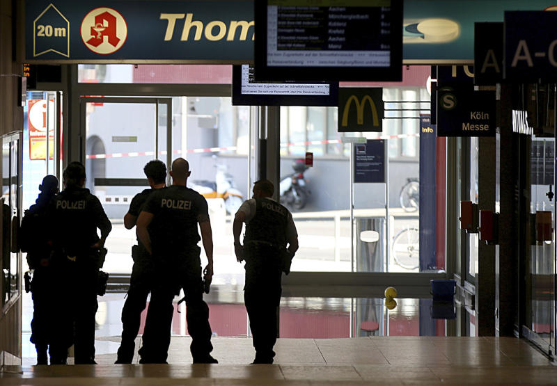 Police forces stand at the Cologne, western Germany, main station Monday, Oct. 15, 2018, after they have closed parts of the station because of a hostage situation. Police said that incident appears to have started Monday at a pharmacy inside the train station. (Oliver Berg/dpa via AP)
