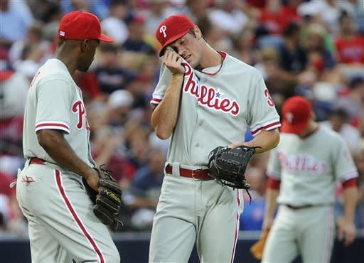 Philadelphia Phillies pitcher Cole Hamels, center, wipes his face as first baseman Ryan Howard, left, looks on, after loading the bases against the Atlanta Braves during the second inning of a baseball game, Friday, July, 27, 2012,in Atlanta. (AP Photo/John Amis)