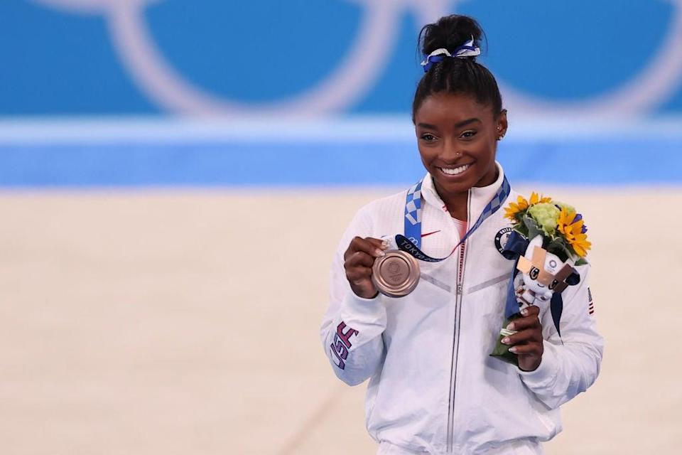 Simone Biles poses with her bronze medal, won in the beam final at Tokyo 2020 on 3 August (Getty Images)