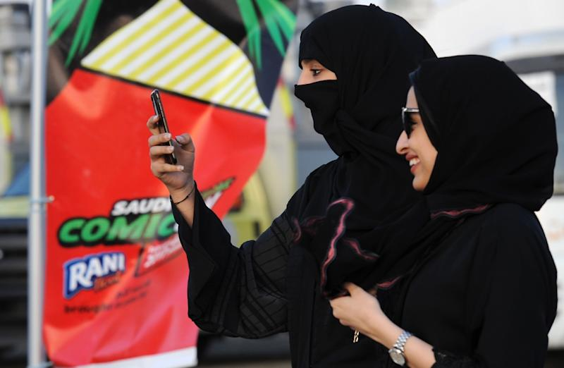 A Saudi woman films using her mobile phone during the first ever Comic-Con event in the coastal City of Jeddah, on February 16, 2017 (AFP Photo/FAYEZ NURELDINE)