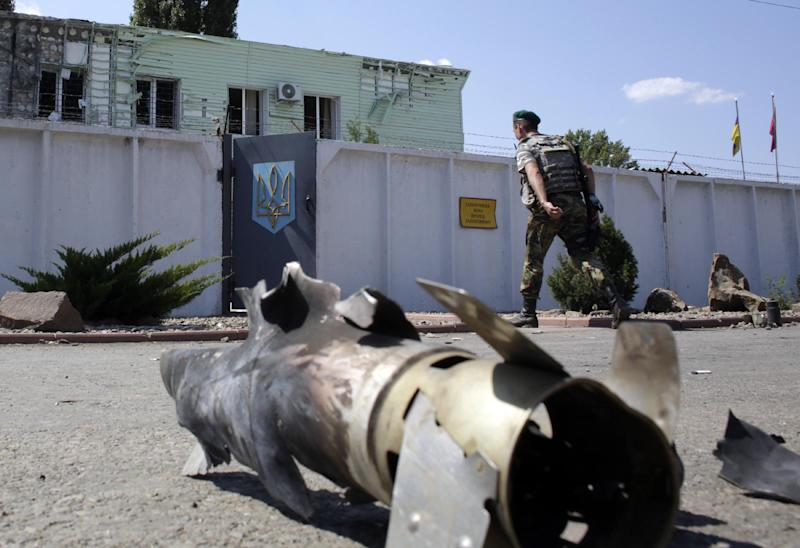 An Ukrainian border guard passes by the wreckage of a rocket as he walks to a barracks following the overnight attack of the frontier guard station in Milove, Lugansk region, on August 8, 2014