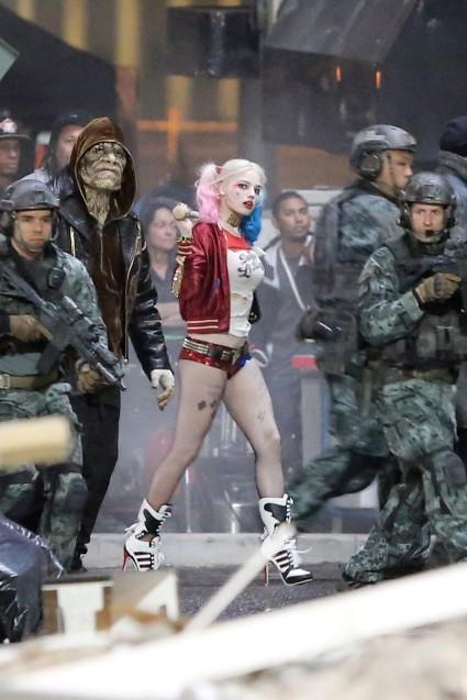 """<strong>Margot Robbie </strong>looks totally badass on the set of Suicide Squad! Director <strong>David Ayer</strong> shared the first full cast photo on Sunday, and now we're getting an even closer look into the colorful world of Harley Quinn. Splash News Robbie can be seen strutting her stuff in full costume on set in Toronto Sunday, complete with a baseball bat, pink and blue dip-dyed pig tails, and a T-shirt that says 'Daddy's Lil Monster.' Splash News She's also sporting plenty of tattoos and a harlequin-themed jacket that reads, 'Property of Joker.' <strong>WATCH: Viola Davis on 'Suicide Squad' Role: 'I'm a Little Scared'</strong> For the uninitiated, Harley Quinn is a supervillain originally created for <em>Batman: The Animated Series</em> in 1992. She was once a doctor at Arkham Asylum who became infatuated and soon hopelessly devoted to a twisted relationship with Joker, whom she adoringly calls """"Mister J"""" in her high-pitched, thick Brooklyn accent. Ayer recently shared a photo of Harley's main man, played by <strong>Jared Leto</strong>. Robbie will star alongside Leto, <strong>Will Smith </strong>(Deadshot), <strong> Joel Kinnaman</strong> (Rick Flagg), <strong> Jai Courtney </strong>(Boomerang), <strong>Cara Delevingne </strong>(Enchantress), <strong>Adewale Akinnuoye-Agbaje</strong> (Killer Croc) and <strong>Viola Davis </strong>(Amanda Waller). The film will follow a group of supervillains, tasked with executing a dangerous and likely fatal mission to have their criminal slates wiped clean. <em>Suicide Squad</em> is scheduled to hit theaters in August 2016. <strong> Follow Ashley on Twitter: @AshCrossan </strong>"""