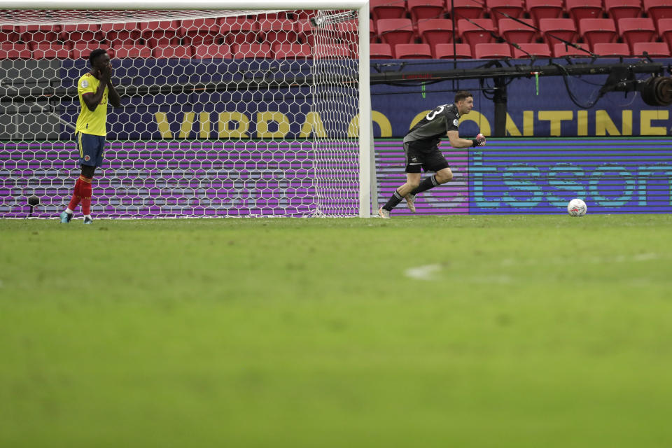 Argentina's goalkeeper Emiliano Martinez, right, reacts after stoping a penalty shot by Colombia's Davinson Sanchez, left, in a the penalty shootout during a Copa America semifinal soccer match at the National stadium in Brasilia, Brazil, Wednesday, July 7, 2021. (AP Photo/Eraldo Peres)