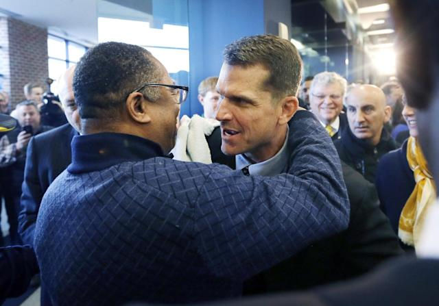 Jim Harbaugh, Michigan's new head football coach is hugged after he was introduced at an NCAA college football news conference Tuesday, Dec. 30, 2014, in Ann Arbor, Mich. (AP Photo/Carlos Osorio)