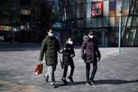 A family wears protective face masks outside an almost-empty Beijing shopping mall