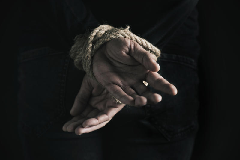 closeup rear view of a man with his hands tied behind his back with rope, against a black background
