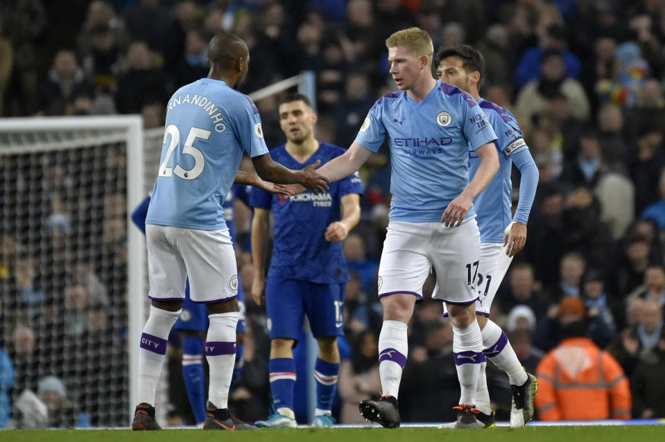 Manchester City's Kevin De Bruyne celebrates with Fernandinho, left, after scoring his side's first goal during the English Premier League soccer match between Manchester City and Chelsea at Etihad stadium in Manchester, England, Saturday, Nov. 23, 2019. (AP Photo/Rui Vieira)