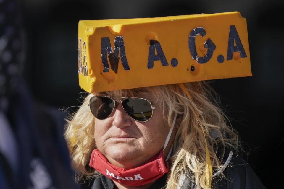 A supporter waits for President Donald Trump to speak at a campaign rally Friday, Oct. 30, 2020, at the Austin Straubel Airport in Green Bay, Wis. (AP Photo/Morry Gash)
