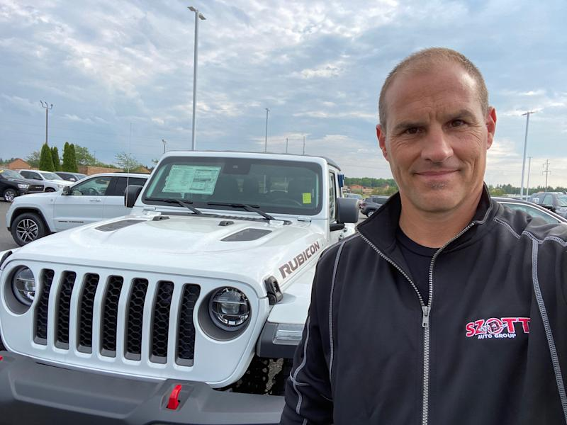 Thad Szott stopped by Feeny Chrysler Jeep Dodge Ram in Gaylord, Michigan as he checked inventory levels around the state and discovered Jeep Wrangler had sold out. Szott, co-owner of Szott Auto Group in White Lake Charter Township, is pictured beside a hot-selling new Jeep Gladiator pickup styled after the Wrangler on July 6, 2020.