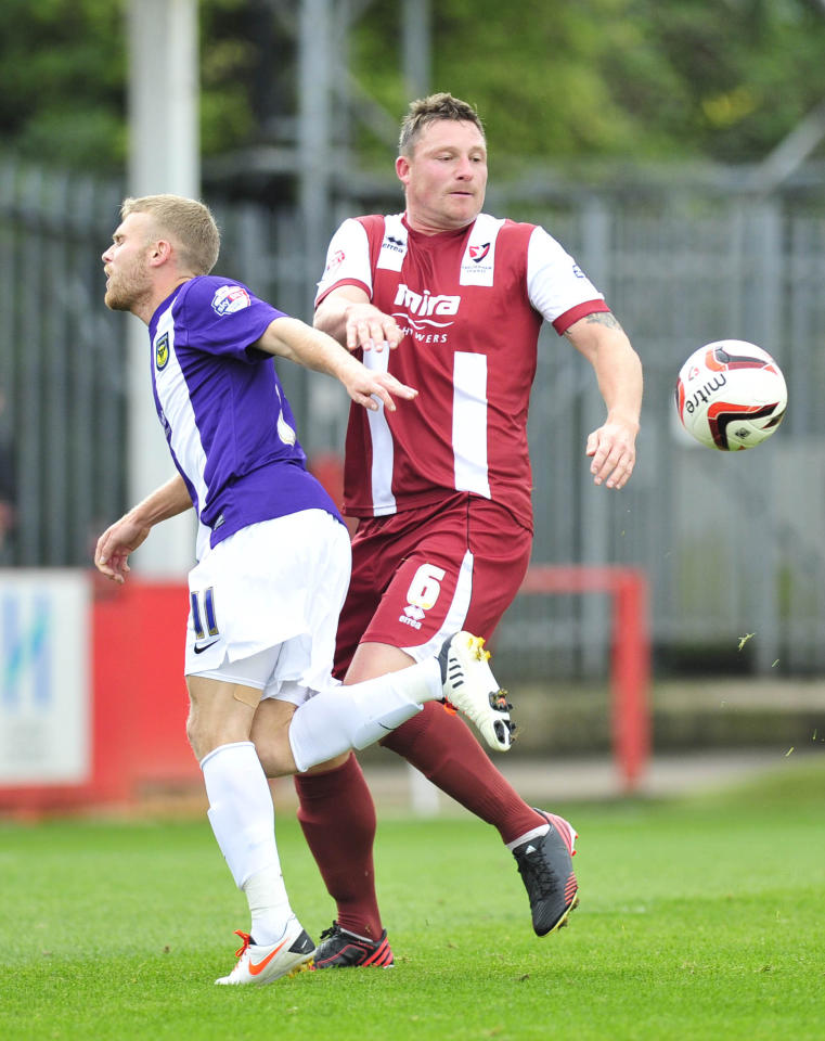 Cheltenham's Steve Elliott and Oxford's Alfie Potteer in action during the Sky Bet League Two match at the Abbey Business Stadium, Cheltenham.
