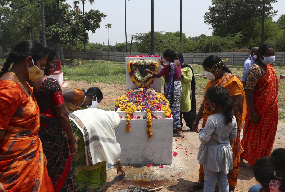 Relatives perform rituals at the grave of a person who died of COVID-19, at a crematorium on the outskirts of Hyderabad, India, Sunday, May 23, 2021. (AP Photo/Mahesh Kumar A.)