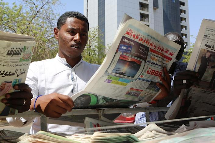 Sudanese man looks at newspapers displayed at a kiosk in the capital Khartoum on February 16, 2015 (AFP Photo/Ashraf Shazly)