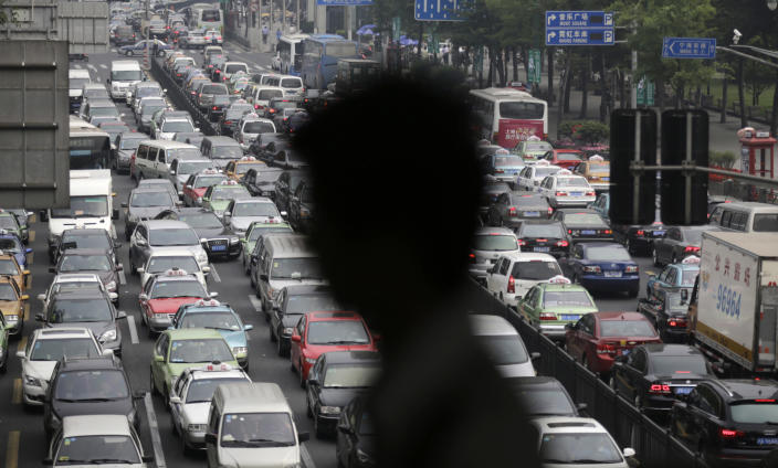 FILE - In this May 29, 2013 file photo, a street becomes clogged with traffic in Shanghai, China. Global warming is triggered by heat-trapping gases, such as carbon dioxide, that stay in the atmosphere for a century. Much of the gases still in the air and trapping heat came from the United States and other industrial nations. China is now by far the No. 1 carbon dioxide polluter, followed by the United States and India. (AP Photo/Eugene Hoshiko, File)