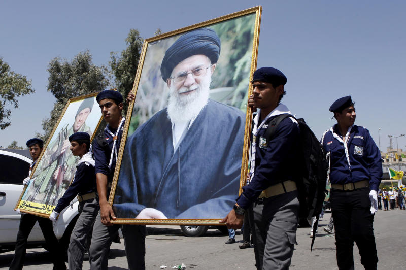 FILE - In this file photo taken on Friday, Aug. 2, 2013, Iraqi Hezbollah scouts parade with a portrait of Iran's supreme leader Ayatollah Ali Khamenei as they mark Al-Quds Day or Jerusalem Day in Baghdad, Iraq, Iraqi officials and militant groups say Iranian-backed Shiite militias are threatening to retaliate against American interests inside Iraq if the United States goes ahead with strikes against Syrian President Bashar Assad's regime, a close ally of Tehran. Iraqi officials say they're taking the threats seriously. Such attacks risk exacerbating the deteriorating security environment inside Iraq. (AP Photo/Hadi Mizban, File)