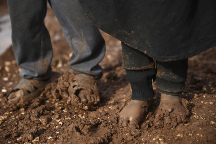 Syrian children stand in a camp for displaced muddied by recent rains near the village of Kafr Aruq , in Idlib province, Syria, Thursday, Jan. 28, 2021. (AP Photo/Ghaith Alsayed)
