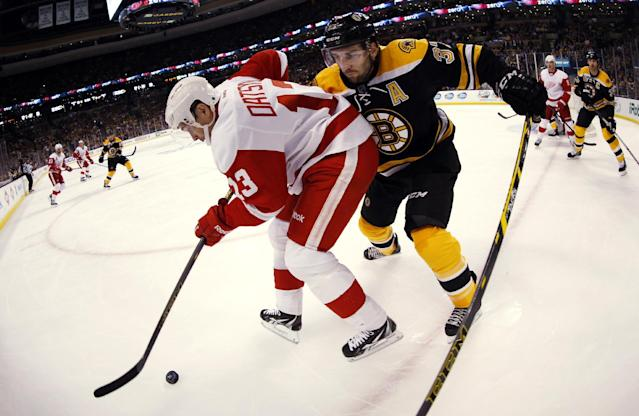 In this photo taken with a fisheye lens, Detroit Red Wings' Pavel Datsyuk (13) tries to keep the puck from Boston Bruins' Patrice Bergeron during the first period of Game 1 of a first-round NHL playoff hockey series in Boston on Friday, April 18, 2014. (AP Photo/Winslow Townson)