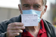 Dr. Michael Roach, a specialist in internal medicine and geriatrics, shows his vaccination card after receiving the Moderna COVID-19 vaccine at a site for health care workers at Ritchie Valens Recreation Center Wednesday, Jan. 13, 2021, in Pacoima, Calif. (AP Photo/Marcio Jose Sanchez)