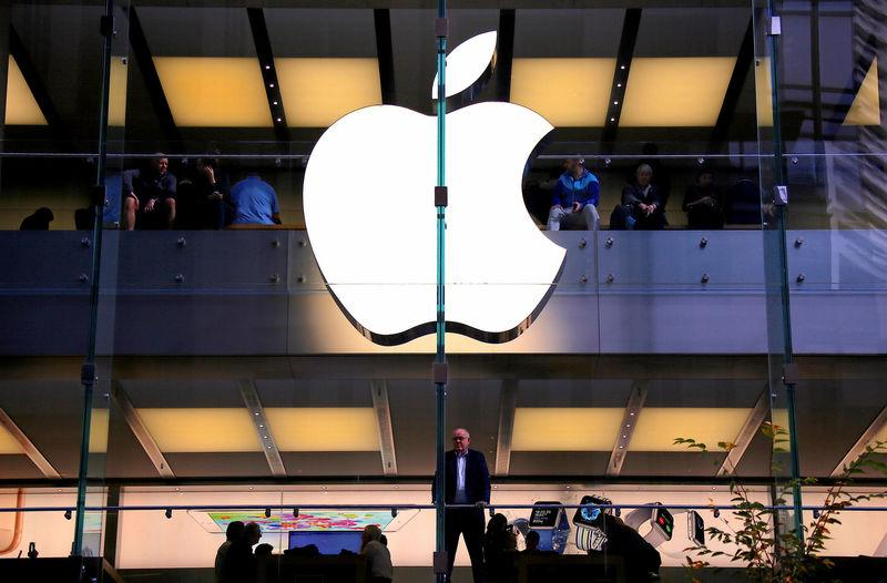 A customer stands underneath an illuminated Apple logo as he looks out the window of the Apple store located in central Sydney
