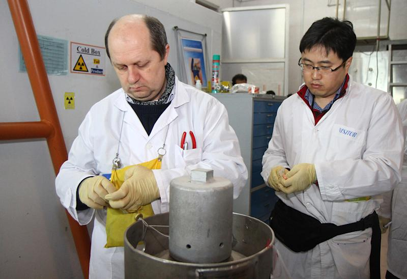 International Atomic Energy Agency inspectors seal after disconnecting the connections between the twin cascades for 20% uranium production at Iran's Natanz nuclear power plant on January, 20, 2014