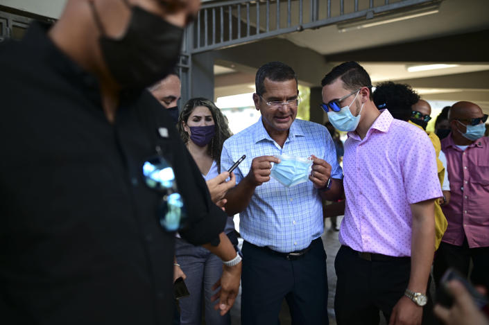 Puerto Rico Gov. Pedro Pierluisi, center, attends a mass vaccination campaign against COVID-19 at the Maria Simmons school in Vieques, Puerto Rico, Wednesday, March 10, 2021. Government officials are urging everyone in Vieques to get vaccinated so the tiny island popular with tourists can achieve herd immunity, but noted that many residents have been reluctant to be inoculated against the new coronavirus. (AP Photo/Carlos Giusti)