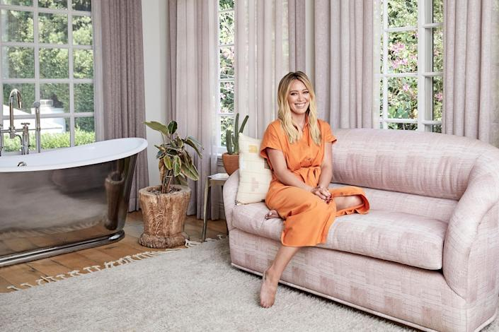 Hilary Duff sits in her bathroom, which is like her own private sanctuary (she even takes guitar lessons in there!) (Jenna Peffley / Architectural Digest)