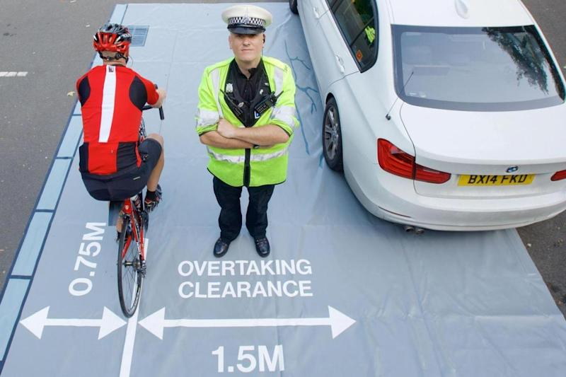 Safety: officer demonstrating a 'close pass mat' which will be offered to police forces to educate drivers (PA)