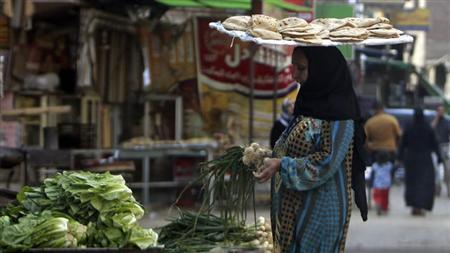 Woman with a tray of bread on her head, buys vegetables near a bakery in Cairo
