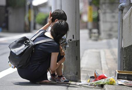A mother and her child mourn for Yua Funato in front of an apartment where she died in Tokyo